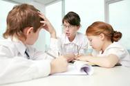 Three little children debating in classroom Stock Photos