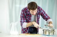 Portrait of man preparing food at kitchen Stock Photos
