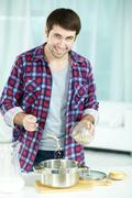Young man pouring oat into saucepan to cook porridge Stock Photos