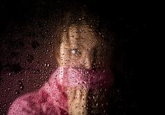Young sad woman portrait behind the window in the rain with rain drops on it Kuvituskuvat