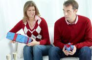 Displeased couple going to exchange gift boxes of different sizes on their speci Stock Photos