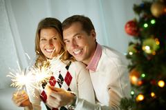 Happy couple burning sparkler on Christmas Eve, looking at camera and smiling Stock Photos