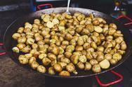 Roasted potatoes cooked in metal cauldron pot Stock Photos