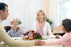 Praying family of four at thanksgiving dinner Kuvituskuvat