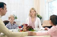 Praying family of four at thanksgiving dinner Stock Photos