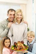 Portrait of happy family of four looking at camera and holding roast turkey Stock Photos