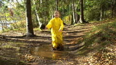 Little girl in a yellow rubber suit is jumping in a puddle. Stock Footage