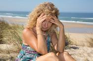 Worried blond girl on the beach sitting on the sand Stock Photos
