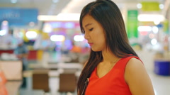 Young Asian Lady drinking orange juice in food court Stock Footage