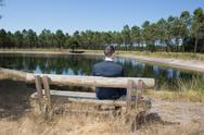 Man sitting alone on park bench, looking down water Stock Photos