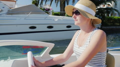 Young woman tourist with sunglasses sitting at the controls of a small boat Stock Footage