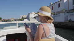 Woman tourist sailing on a small boat on the canal. Use mobile phones Stock Footage