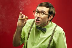 Suspicious nerd smoking a cigar and looking at camera Stock Photos