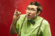 Suspicious nerd smoking a cigar and looking at camera Stock Photos
