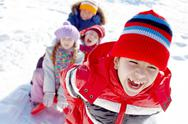 A boy carrying his three friends on sled in sunny winter day Stock Photos