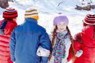 Little girl arm in arm with her friends standing back to the spectator in winter Stock Photos