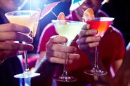 Close-up of three martini glasses in hands of young people Stock Photos