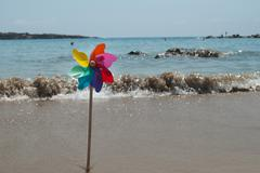 Rotating colorful rainbow pinwheel on the beach coast Stock Photos