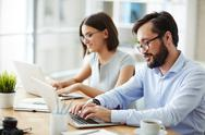 Man and woman working in office at laptop Stock Photos