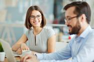 Young businesswoman looking at her male colleagues in office Stock Photos