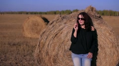 Girl in a black jacket and sunglasses standing near haystack Stock Footage