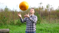 Handsome farmer throw up large pumpkin, happy of fair yield, slow motion Stock Footage