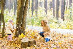 Happy family mother and child girl playing throw leaves in autumn park outdoors Stock Photos