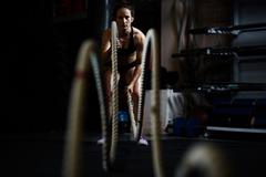 Young woman during cross training with ropes Stock Photos