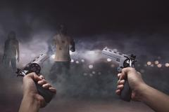 Man with two guns in his hand ready to shooting a lot creepy zombie Stock Photos