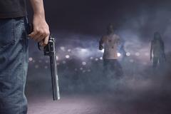 Brave man with jeans pants holding gun looking at zombies Stock Photos