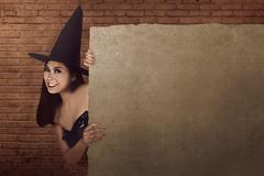 Beautiful asian woman with hat and witch costume hiding and peek form behind  Stock Photos