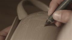 Sculptor Master Sculpt Pattern on Ceramic teapot Stock Footage