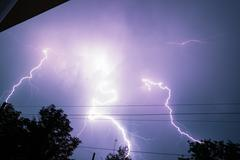 Thunderbolt over the house and dark stormy sky on the background Stock Photos