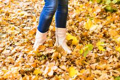 Conceptual image of legs in boots on the autumn leaves. Feet shoes walking in Stock Photos