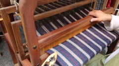 Craftsman weaves a fabric with an ancient hand loom using the wire and t Stock Footage