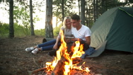 Couple smiling looking at map near bonfire in forest at sunset Slow motion Stock Footage