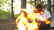 Couple smiling looking for route on map near bonfire in forest Slow motion Stock Footage