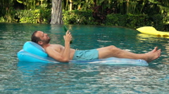 Happy man drinking beer lying on air mattress in pool, super slow motion 240fps Stock Footage