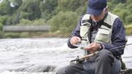 Fly-fisherman sitting on rock, choosing fly Stock Footage