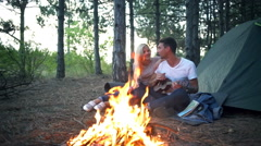 Couple smiling sitting near bonfire in forest Man playing ukulele Slow motion Stock Footage