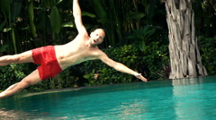 Happy man jumping into swimming pool, super slow motion 240fps Stock Footage