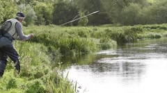 Flyfisherman fishing from riverbank, Irish countryside Stock Footage