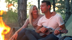 Couple kissing sitting near bonfire in forest Man playing ukulele Slow motion Stock Footage