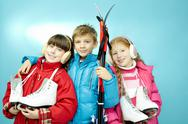 Portrait of three little children with skates and skis looking at camera and smi Stock Photos