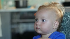 Baby girl sitting on the sofa and watching TV Stock Footage
