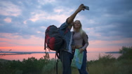 Couple of travelers smiling making selfie on hill at sunrise Slow motion Stock Footage