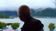 Asian senior man sitting alone and look out to mountain and lake view Stock Footage