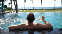 Man with beer relaxing in swimming pool in garden, super slow motion 240fps Stock Footage