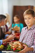 Smiling boy holding thanksgiving poultry, his family eating in the background Stock Photos