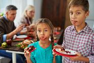 Boy and girl eating sweet pie with dirty mouths, their parents eating in the bac Stock Photos
